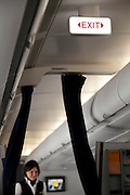 lighted up emergency exit sign inside a passenger airplane