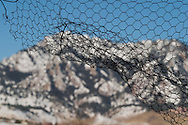 The Rocky Mountains as seen through a mesh wire window in an old farmhouse near Boulder, Colorado