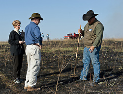 "Josh Hoy, owner of the Flying W Ranch near Clements, Kansas answers unidentified visitors' questions about recently burned prairie at the ""Flames in the Flint Hills"" held at  the ranch. This agritourism event allows ranch guests to take part in lighting the prescribed burns. Prairie grasses in the Kansas Flint Hills are intentionally burned by land mangers and cattle ranchers in the spring to prepare the land for cattle grazing and help maintain a healthy tallgrass prairie ecosystem. The burning is also an effective way of controlling invasive plants and trees. The prairie grassland is burned when the soil is moist but grasses are dry. This allows the deep roots of the grasses to survive and the burned grasses on the soil surface return as nutrients to the soil. These nutrients allow for the rapid growth of new grass. After approximately two weeks of burning, new grass emerges. Less than four percent of the original 140 million acres of tallgrass prairie remains in North America. Most of the remaining tallgrass prairie is in the Flint Hills in Kansas."