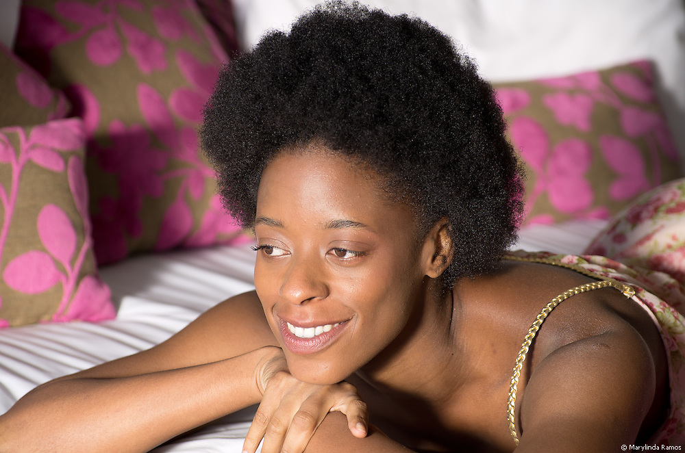 African American woman lying on belly on bed, dressed, looking out the window with a contented smile.