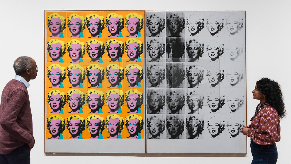 """© Licensed to London News Pictures. 10/03/2020. LONDON, UK. Staff pose next to """"Marilyn Diptych"""", 1962, by Andy Warhol. Preview of """"Andy Warhol"""", a retrospective of over 100 works by one of the most recognisable artists of the late 20th century.  The exhibition runs 12 March to 6 September 2020 at Tate Modern.  Photo credit: Stephen Chung/LNP"""