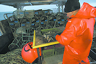 Fisherman John Macgregor, aboard the boat he part-owns named My Amber, cuts herring used for bait in his creels as he sets off at first-light to fish for prawns off Scotland's west coast in a marine 'box' in the inner sound of Rona which restricts entry to large trawlers looking for white fish and allows around 16 creelers unrestricted fishing.