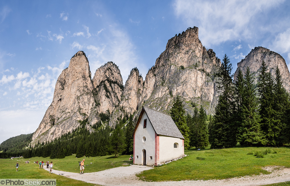 Saint Sylvester's Chapel (San Silvestro) in Vallunga is dedicated to the patron saint of cattle and contains 300-year-old frescoes (depicting the life of Jesus), in Val Gardena, Dolomites, South Tyrol, Italy, Europe. Vallunga/Langental valley is preserved in Puez-Geisler Nature Park. The beautiful ski resort of Selva di Val Gardena (German: Wolkenstein in Gröden; Ladin: Sëlva Gherdëine) makes a great hiking base in the Dolomites, in the South Tyrol region (Trentino-Alto Adige/Südtirol) of Italy. For our favorite hike in the Dolomiti, start from Selva with the first morning bus to Ortisei, take the Seceda lift, admire great views up at the cross on the edge of Val di Funes (Villnöss), then walk 12 miles (2000 feet up, 5000 feet down) via the steep pass Furcela Forces De Sieles (Forcella Forces de Sielles) to beautiful Vallunga (trail #2 to 16), finishing where you started in Selva. The hike traverses the Geisler/Odle and Puez Groups from verdant pastures to alpine wonders, all preserved in a vast Nature Park: Parco Naturale Puez-Odle (German: Naturpark Puez-Geisler; Ladin: Parch Natural Pöz-Odles). UNESCO honored the Dolomites as a natural World Heritage Site in 2009. This panorama was stitched from 4 overlapping photos.