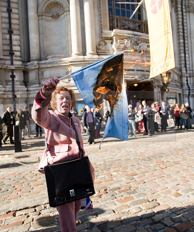 © Licensed to London News Pictures. 22/10/2011. London, UK. Hazel Prowse burning a European Union flag following The People's Pledge campaign at Westminster Methodist Central Hall today (22/10/2011) two days before the vote in Parliament on whether there should be an EU referendum. Photo credit: Ben Cawthra/LNP