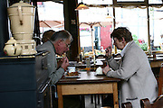 Belgium Restaurant a mature couple eating apple cake and cream with their coffee
