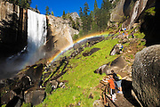 Hikers on the Mist Trail enjoying a rainbow under Vernal Fall, Yosemite National Park, California USA