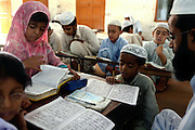 Muslim children are studying the Koran, Islam's holy book, at a large Madrassa (Islamic school) in North-West Karachi, Pakistan's main economic hub.
