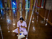 31 DECEMBER 2017 - BANGKOK, THAILAND: A woman meditates on New Year's Eve in the prayer hall at Wat That Thong in Bangkok. The strings will connect people who come to the temple later and will serve to amplify their prayers. Many Thais go to temples and shrines to pray and meditate during New Year's Eve and New Year's Day.    PHOTO BY JACK KURTZ