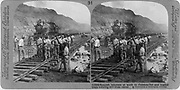 Construction of the Panama Canal: Spanish labourers at work in the Culebra Cut (Gaillard Cut) . A loaded steam train hauls spoil from the site.  The canal, a great feat of civil engineering, was opened in 1914. Photograh.