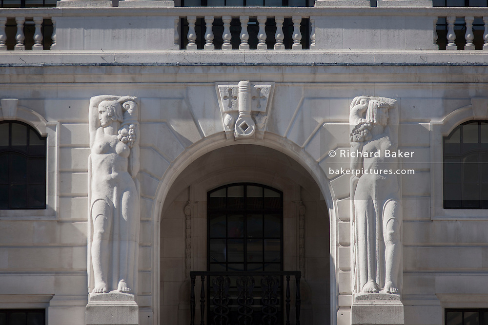 Mythical Greek Caryatids sculpture in Portland stone aside the central arch on the exterior of the Bank of England in the City of London. The two female caryatid figures, their torsos nude, but with thin drapery covering the lower parts of their bodies. Each supports a cornucopia on her shoulder and looks away from the arch, and across her raised arm, towards the two male figures beyond.