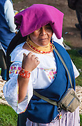 "A woman with purple head covering sells a cow at the bustling Saturday animal market in Otavalo, Ecuador, South America. The culturally vibrant town of Otavalo attracts many tourists to a valley of the Imbabura Province of Ecuador, surrounded by the peaks of Imbabura 4,610m, Cotacachi 4,995m, and Mojanda volcanoes. The indigenous Otavaleños are famous for weaving textiles, usually made of wool, which are sold at the famous Saturday market and smaller markets during the rest of the week. The Plaza del Ponchos and many shops tantalize buyers with a wide array of handicrafts. Nearby villages and towns are also famous for particular crafts: Cotacachi, the center of Ecuador's leather industry, is known for its polished calf skins; and San Antonio specializes in wood carving of statues, picture frames and furniture. Otavaliña women traditionally wear distinctive white embroidered blouses, with flared lace sleeves, and black or dark over skirts, with cream or white under skirts. Long hair is tied back with a 3cm band of woven multi colored material, often matching the band which is wound several times around their waists. They usually have many strings of gold beads around their necks, and matching tightly wound long strings of coral beads around each wrist. Men wear white trousers, and dark blue ponchos. Otavalo is also known for its Inca-influenced traditional music (sometimes known as Andean New Age) and musicians who travel around the world. Published in ""Light Travel: Photography on the Go"" book by Tom Dempsey 2009, 2010."