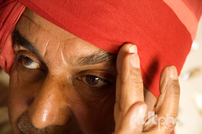 A man from Rajasthan, India, gives the last touch to his turban by fixing its position on the eyebrow. Such position corresponds to a sign of power