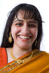 Woman wearing traditional Asian dress and jewellery smiling,
