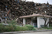 Cleared debris is piled up behind a public lavatory in Minamisanriku, Miyagi Prefecture, Japan on 07 Sept. 2011. Authorities are unable to dispose of much of the debris created by the March disasters due to fears of radiation contamination, leading to giant mounds of waste that are becoming increasingly more toxic. Photograph: Robert Gilhooly