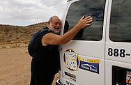 Guest Michael Winston hugs the van that will take him back to the Biggest Loser Resort in Ivins, Utah after he completed a 5 mile hike September 7, 2010.  Guests at the resort affiliated with the popular reality television show have a daily hike of several miles and workout in an aerobics room, a gym and a swimming pool for 6 to 7 hours each day.  REUTERS/Rick Wilking (UNITED STATES)