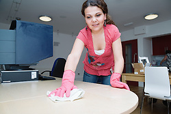 Eastern European working as cleaner wiping office desk,