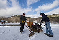"Chief ""shoveler"" Bill Sharkey keeps the ice clear for ""sawyer"" Dave Lacasse as he cuts ice blocks during the first day of Rockywald Deephaven Camp's annual Ice Harvest on Squam Lake Wednesday.  Karen Bobotas for the Laconia Daily Sun"