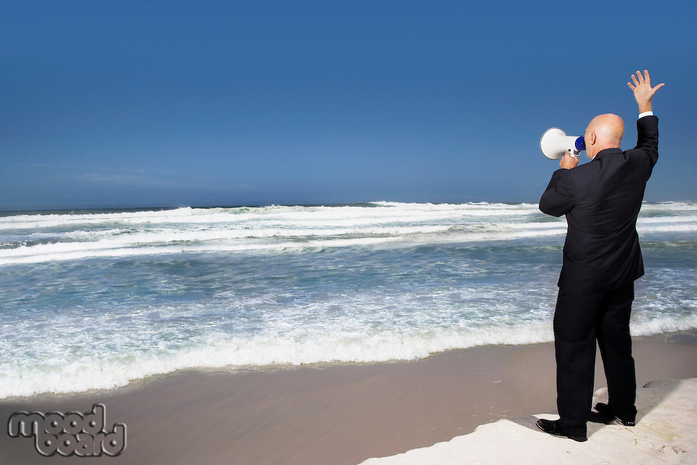 Business man standing on edge of sea using megaphone back view