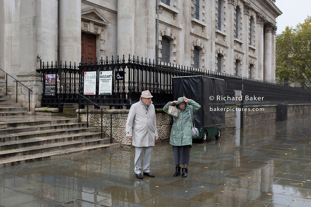 Two visitors to the capital endure heavy rainfall on an autumn afternoon outside St. Martin-in-the-Fields church on Trafalgar Square, on 24th October 2019, in Westminster, London, England.