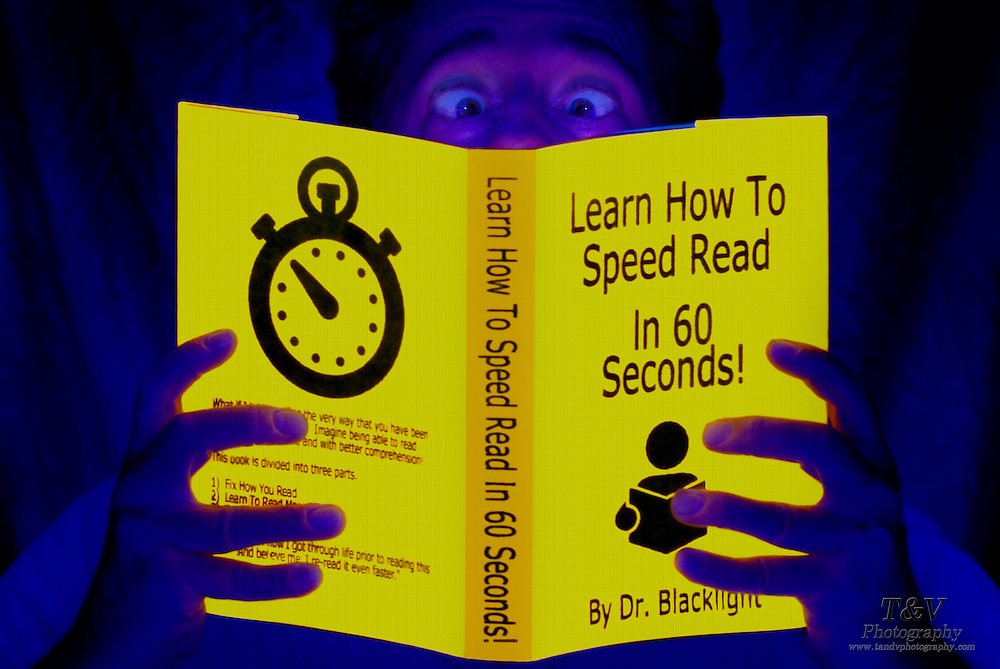 "Man crosses his eyes while reading a glowing booked titled ""Learn How To Speed Read In 60 Seconds"".Black light"
