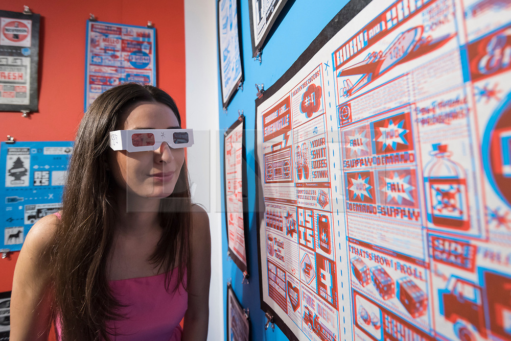 © Licensed to London News Pictures. 04/10/2018. LONDON, UK. A staff member wears 3D glasses to view work by New York artist Skewville. Preview of Moniker Art Fair, taking place during Frieze Week at the Old Truman Brewery, near Brick Lane.  Now in its tenth year, the fair embraces contemporary urban art from emerging and established artists  This year, the show's theme is 'Uncensored', shedding light on social, economic and ecological issues, and is open 4 to 7 October.  Photo credit: Stephen Chung/LNP