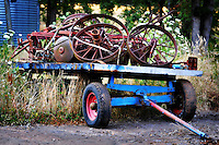 An old blue and red wagon trailer loaded with antique metal wagon wheels and parts
