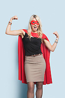Portrait of excited young blond woman in superhero costume flexing arms over light blue background