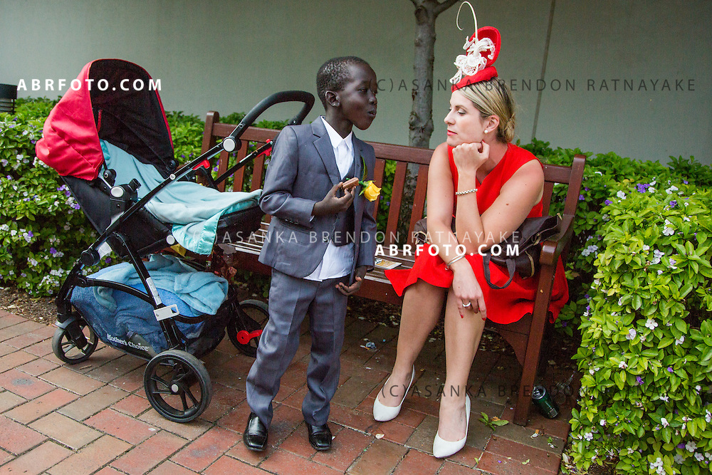 MELBOURNE, AUSTRALIA - NOVEMBER 3 : A woman in a red dress and a young boy dressed in a suit have a conversation during the 2015 Melbourne Cup Day at Flemington Racecourse. Melbourne, Australia November 3 2015.