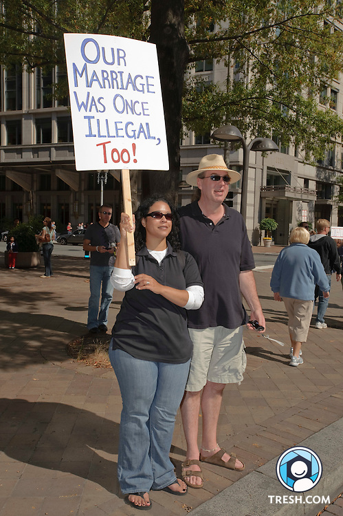 """Interracial couple Tiffany and Mike Newman hold a sign that reads """"Our Marriage Was Once Illegal, Too!"""" at the side of the National Equality March, October 11, 2009 in Washington, DC."""