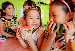 August 7, 2017 - Lianyungang, Lianyungang, China - Lianyungang, CHINA-August 7 2017: (EDITORIAL USE ONLY. CHINA OUT) Children enjoy watermelons in Lianyungang, east China's Jiangsu Province, August 7th, 2017, marking the solar term of Start of Autumn. It¡¯s a Chinese tradition to bite and enjoy fruits on the day of Start of Autumn. The traditional Chinese lunar calendar divides the year into 24 solar terms. Start of Autumn, the 13th solar term of the year, begins this year on Aug 7 and ends on Aug 22. Start of Autumn reflects the end of summer and the beginning of autumn. The fruitful season is approaching. (Credit Image: © SIPA Asia via ZUMA Wire)