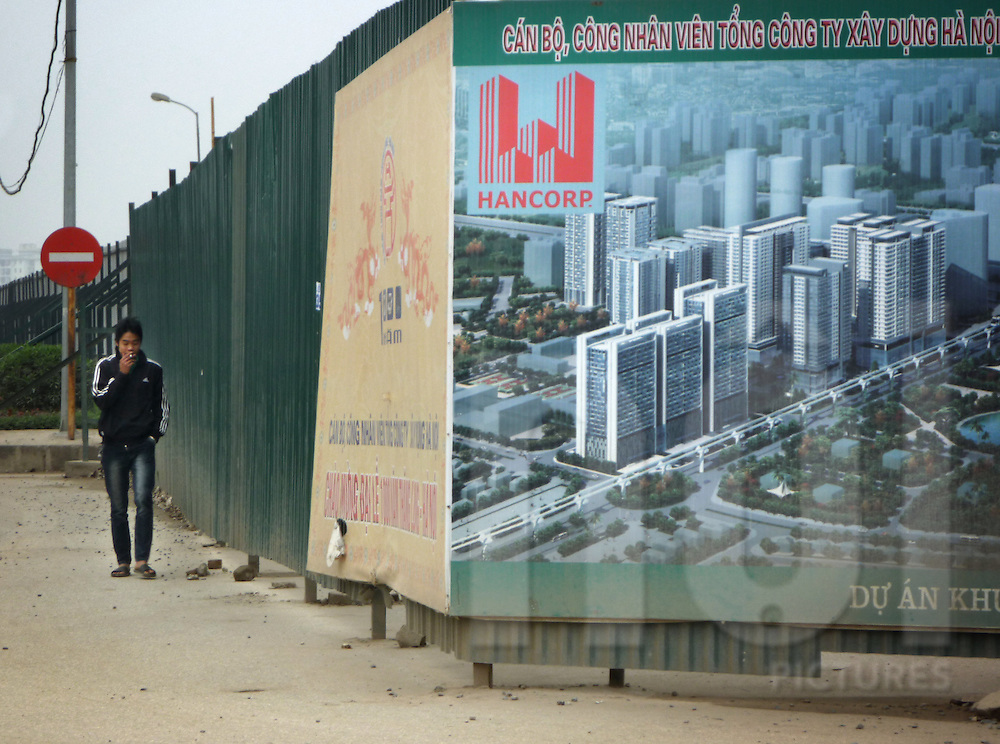 a young man is smoking a cigarette and walks along a billboard showing urban development project in Cau Giay district, Hanoi, Vietnam