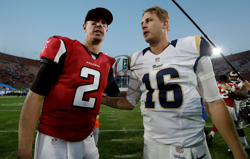 Atlanta Falcons quarterback Matt Ryan, left, and Los Angeles Rams quarterback Jared Goff meet on the field after an NFL football game Sunday, Dec. 11, 2016, in Los Angeles. The Falcons won 42-14. (AP Photo/Rick Scuteri)