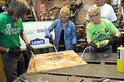 Restoration expert Nicole Curtis, center, Nan Smith, of Staten Island MakerSpace, and Terry Scott, left, of Rebuilding Together, use Bernzomatic blowtorches to patina a sign at the launch event for the Bernzomatic Find Your Fire Community Grants program, Thursday, Oct. 22, 2015, in New York.  MakerSpace is a community center still feeling the effects of Hurricane Sandy three years later.  Bernzomatic, the industry leader in handheld torches, is encouraging people to submit a community project for a chance to win one of three $10,000 grants and a visit from Curtis. Go to Bernzomatic.com/Grants for more information. (Photo by Diane Bondareff/Invision for Bernzomatic/AP Images)