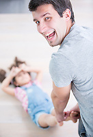 Rear view portrait of happy father dragging daughter on floor at home