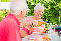 A mature couple enjoying a meal outside on their patio with a glass of wine.<br />