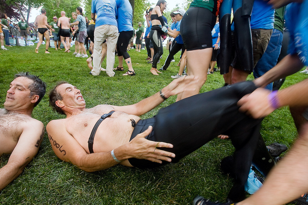 JEROME A. POLLOS/Press..Cliff Bonnell-Jones, from Chelan, Wash., left, and Steve Young, from Taylorsville, Utah, have their wetsuits removed in the transition area following the 2.4-mile swim Sunday during the Ford Ironman Coeur d'Alene.