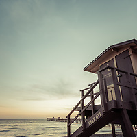 San Clemente lifeguard tower one retro photo. Incudes the San Clemente Pier at sunset. San Clemente California is a popular beach city in Orange County in the United States of America. Photo is high resolution and Copyright ⓒ 2017 Paul Velgos with All Rights Reserved.