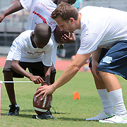 Casey Barth helps Tre' Mckinnon, 8 place a football Sunday July 13, 2014 during a kicking clinic at Hoggard High School in Wilmington, N.C. (Jason A. Frizzelle)