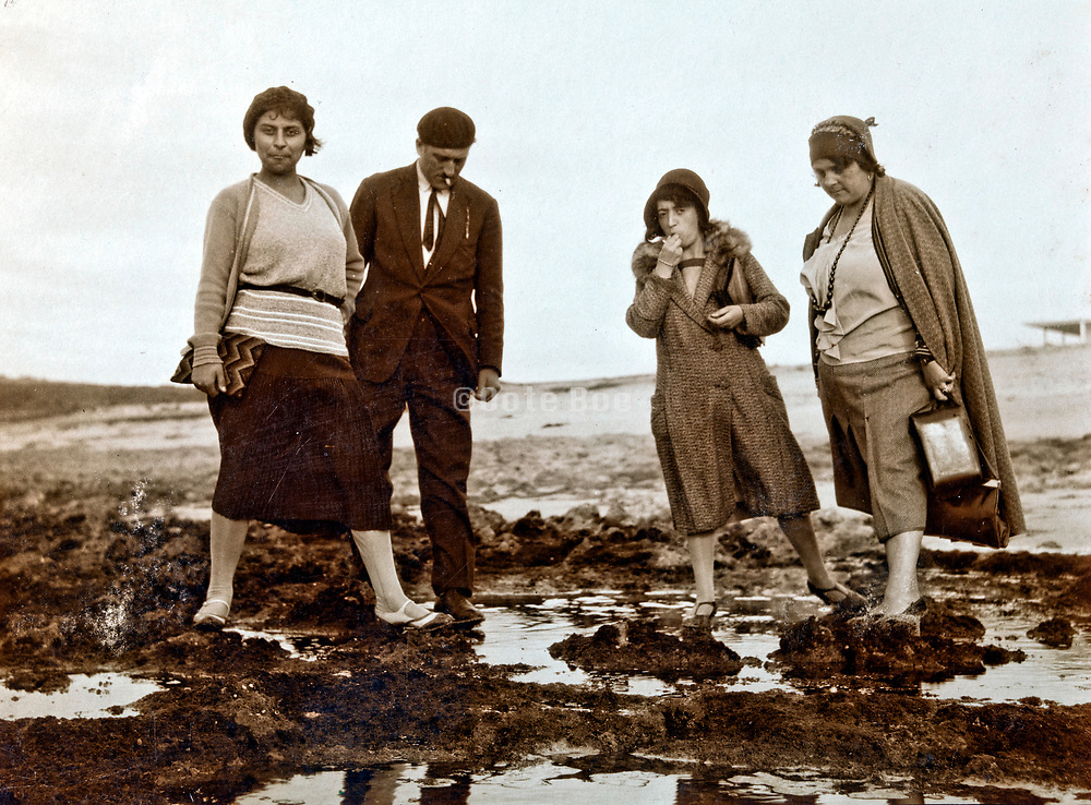 well dressed adult people standing in a wet muddy field 1930s