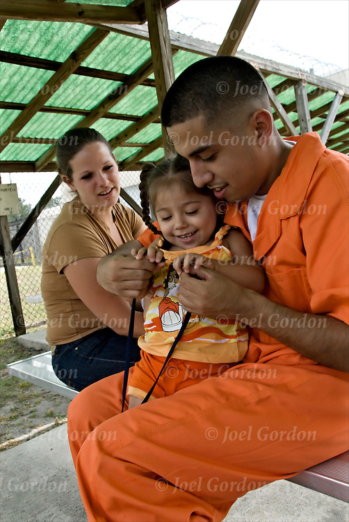 Hispanic American Trusty Inmate visited by wife and 2 1/2 year old and 9 month of child.Orange Jump Suit #14V.release # 2414, 2415.Family visits inmate (trustee) in medium security outdoor execise yard durning twice weeking visitation in the Putnam County Jail  FL.