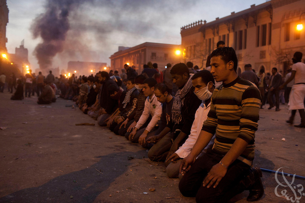 As Egyptian security vehicles burn in the background, Egyptian protesters take time out to pray on Ramsis street during massive and unprecedented demonstrations January 28, 2011 across Cairo, Egypt . The protests, inspired by the recent revolution in Tunisia, have struck a chord with Egypt's population, tired of inflation, high unemployment and alleged corruption within the Mubarak government..Slug: Egypt.Credit: Scott Nelson for the New York Times
