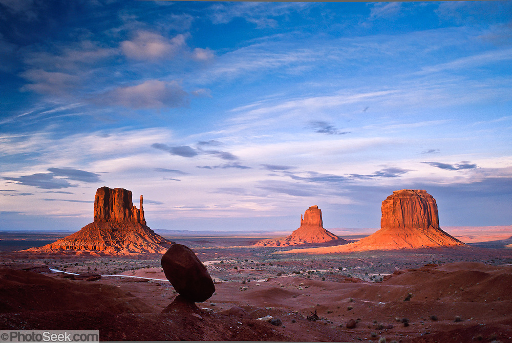 Left and Right Mittens, Merrick Butte, and a balanced rock punctuate the horizon in Monument Valley Navajo Tribal Park, Arizona, USA. The Western movie director John Ford set several popular films here.