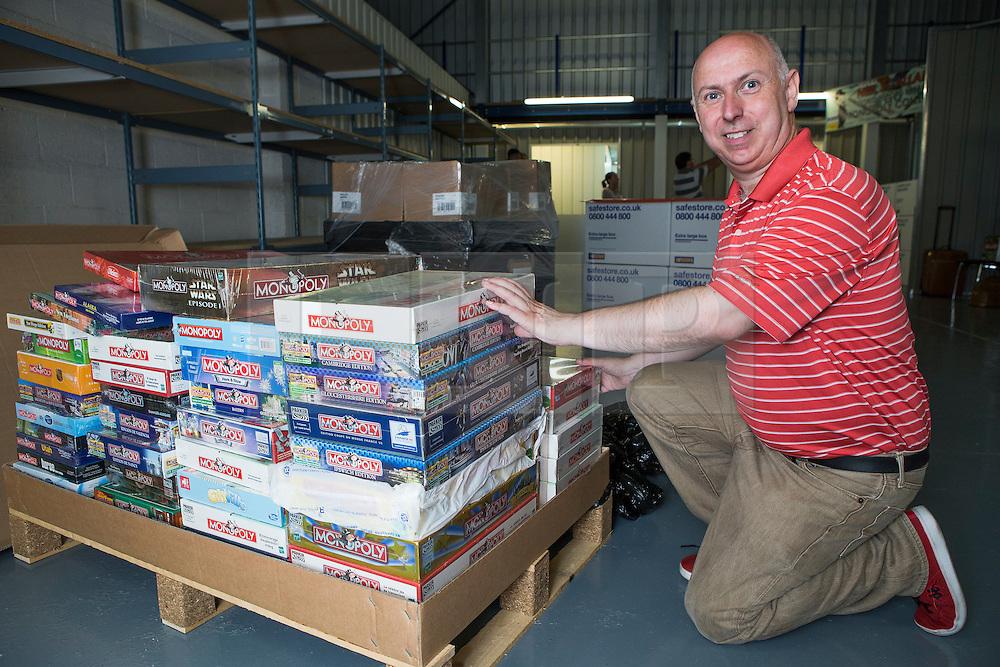 ** CAPTION CORRECTION Neil Scallan has spent an estimated £150,000 on monopoly boards, not £150,00 as stated in previous captions** <br /> © Licensed to London News Pictures. 24/07/2016. Crawley, UK.  Monopoly board game collector Neil Scallon next to some of his 2200 unopened monopoly games, which he is hoping will set a Guinness World Record for the largest collection of Monopoly.  Scallan, who has been collecting for 10 years and estimates he has spent over £150,00 on the board games, is expected to set a  world record at the count later today (Sun) as the previous world record stands at around 500..  Photo credit: Grant Melton/LNP