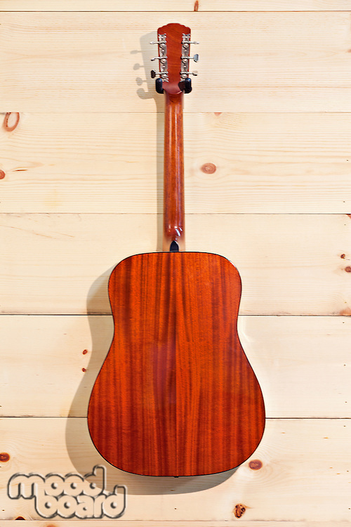 Gibson red guitar on wood grain wall