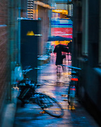 Night Reflections in a rainy alleyway - A sudden movement in the alley beside me, wrapped in the glowing street lights and rain, had me quickly frame and try to capture the departing subject while panning slightly with the accidentally slow shutter speed.<br /> <br /> f 8 @ 1/4 s, 3200 ISO<br /> 28.0-300.0 mm f/3.5-5.6 at 105 mm on NIKON D750