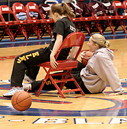 Michelle Nemeth (left) slides in, and pushes TeeJay Dorrough off the last remaining seat to win at basketball chairs during halftime of a UD Women's basketball game at the University of Dayton Arena, January 21, 2007.  As the winner, Michelle received a t-shirt.  Starting with six girls and six chairs, they were required to go to a basket, sink a shot, and return.  While they were shooting, a chair was removed.
