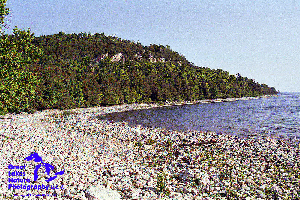 The Niagara Escarpment, a geological formation that runs westward from New York State, through Ontario, Michigan, Wisconsin, and Illinois, is visible when looking south from the shoreline at Tennison Bay in Door County Wisconsin's Peninsula State Park.