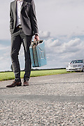 Low section of young businessman carrying petrol can with broken car in background at countryside