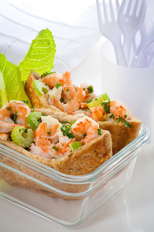 Shrimp Salad Pita Bread sandwich,in clear glass dish on top of colorful napkin,white background