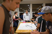 Students in We Are First, a group of first generation college students, decorate a banner for the Homecoming parade in the First Scholars House on Tuesday, October 6, 2015. Photo by Kaitlin Owens